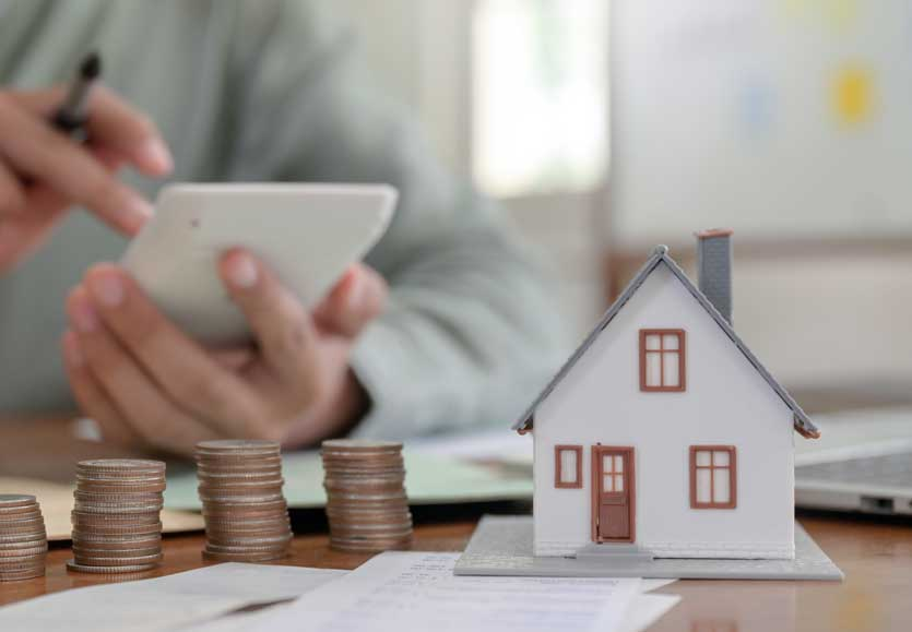 Estate Planning close up shot of houses models and coins with a mans hand on calculator