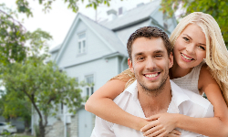 Young happy couple in front of house after a real estate appraisals