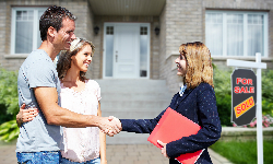 Couple and Real Estate Agent shaking hands on new home
